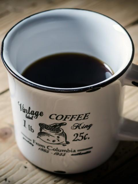 halb gefüllte Vintage Kaffeetasse auf Holztisch
