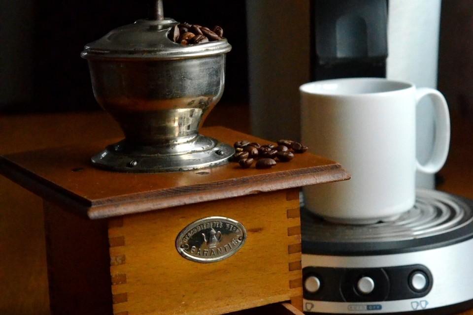 kleine Kaffeemühle vor einer Senseo Kaffeemaschine